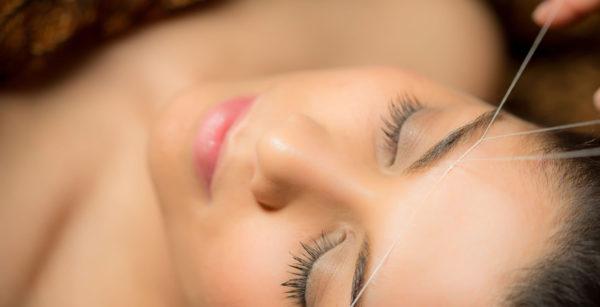 Black Haired Millennial Woman Receiving Eyebrow Threading